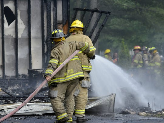 Firefighters spray debris after a fire at 82 Overlake