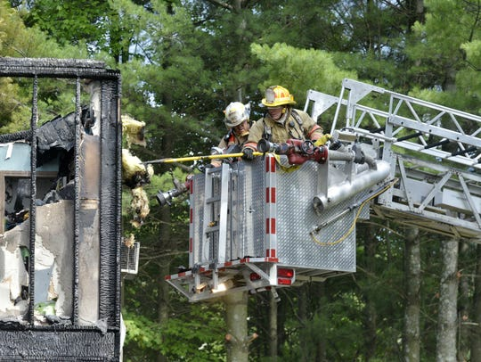 Fire crews conduct salvage efforts after a fire at