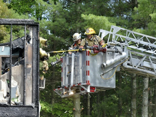 Fire crews conduct salvage efforts after a fire at 82 Overlake Drive in Milton destroyed a home Tuesday.