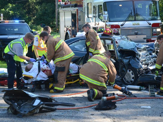 Emergency workers remove a passenger from one of the cars.