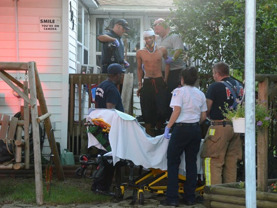 A young man shot Friday is helped to a stretcher.