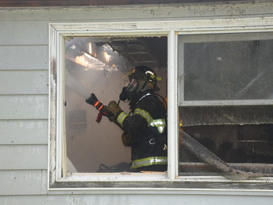 A firefighter works inside the structure.
