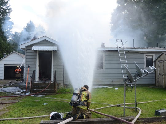 Firefighters dump water into the damaged duplex as they attempt to douse all the hot spots.