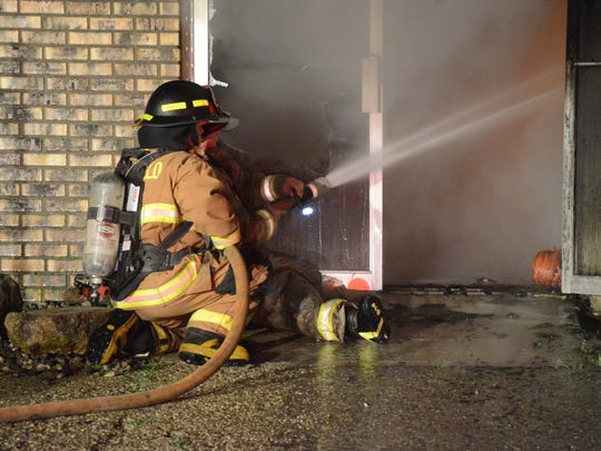 Firefighters pour water on the fire through an open door.