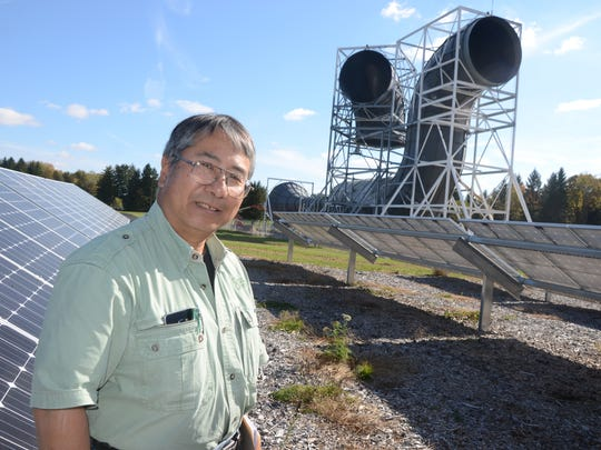 Art Toy, of Four Elements Energy standing near the solar panels and the wind funnel at Fort Custer Training Center. His company installed the solar panels.