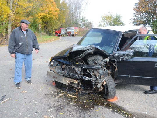 Dave Byrd inspects the damage to his vehicle after a crash Monday morning.