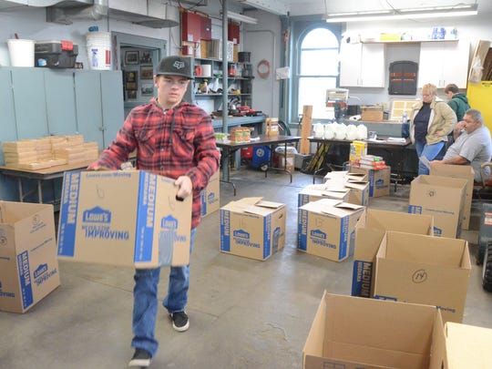 Collin Fleming carries a box with a Thanksgiving meal packed at a Battle Creek fire station.