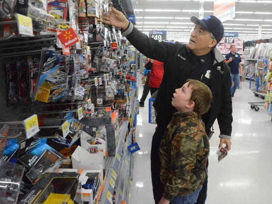 Izaak Oldenburg, 10, had help from a taller Officer Marc Pierce of the Kellogg Community Police Department during Shop With  A Cop.