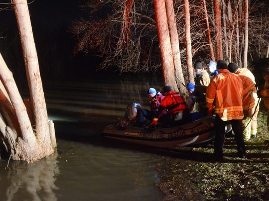 Battle Creek firefighters prepare to launch a small boat Saturday near Jackson Street and Stringham Road to search for a car in the Kalamazoo River.
