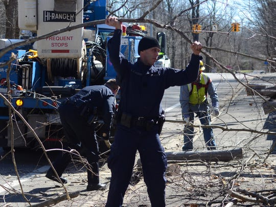 Battle Creek Police Officer Kevin Stansbery helps clear debris after a tree limb was blown into wires and the roadway.