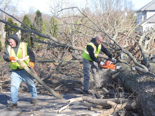 Battle Creek employees Tom Harmon, left, and Chaz Wilkey clear tree which fell across South Helmer Road south of Tiffany Lane.