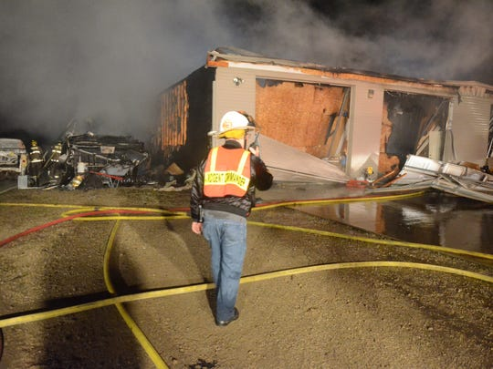 Bedford Township firefighters said a fire early Sunday began in a camper parked (left) on the side of the building.