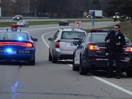 Battle Creek officer Craig Wolf stands near a car stopped on the entrance ramp to I-94 following a traffic stop by the Michigan State Police.