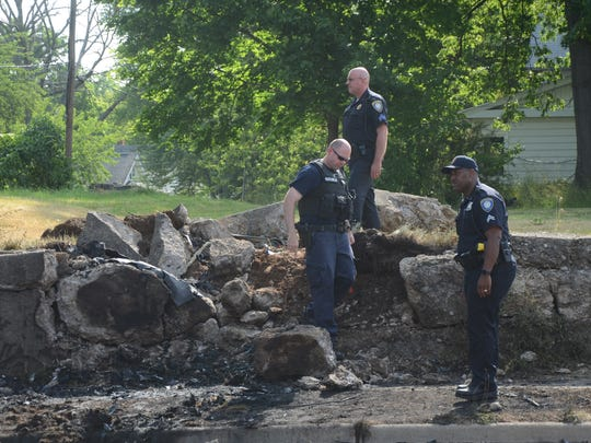 Police officers inspect the damage to the retaining wall after the damaged car was removed.