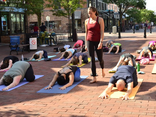 Mackenzie Doyle, standing, leads a yoga class on Church Street on Sunday, June 18, 2017. The class is part of a summer-long series put on by Sukha Yoga where donations are given to a different local nonprofit each week.