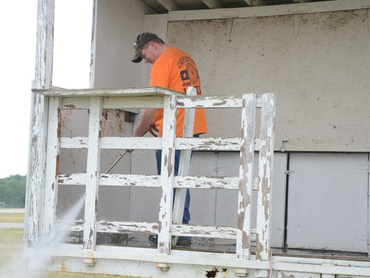 Jeff Taylor of Carpenters Local Union 525 uses a power washer before painting the announcer's stand for the Field of Flight.