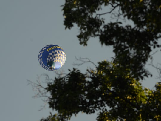 The hot air balloon Freedom flies above the trees.