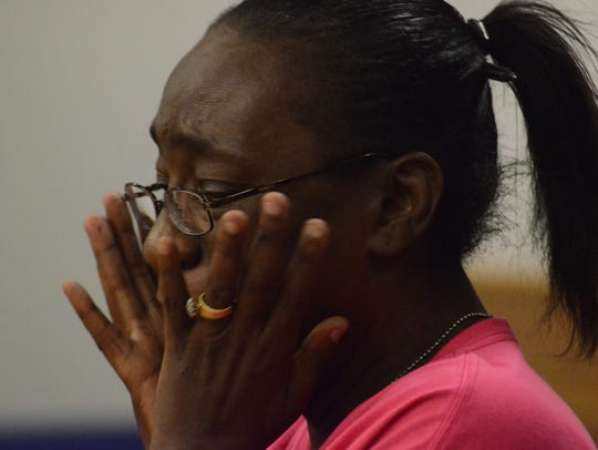 Rena Pratcher holds her face as she tells the judge