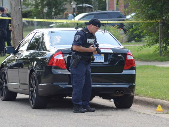 Police search for evidence at the scene of the Sunday shooting.