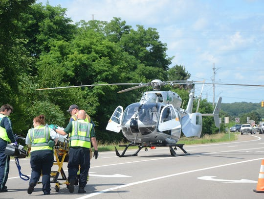 Paramedics take an injured woman to a medical helicopter