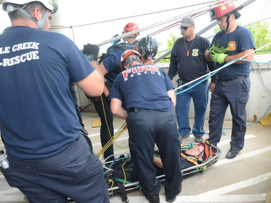 Firefighters strap Captain Dan Wolfe to the rescue