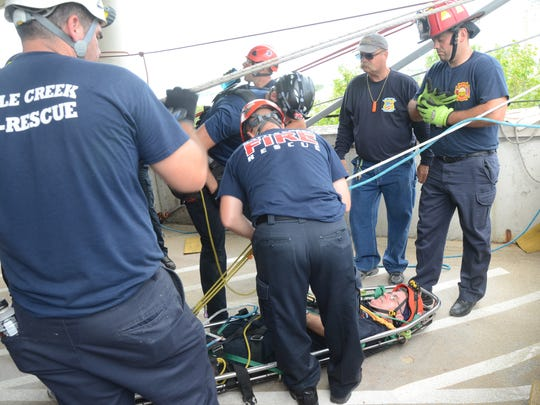 Firefighters strap Captain Dan Wolfe to the rescue basket before he is lowered to the ground Thursday, Aug. 3, 2017.