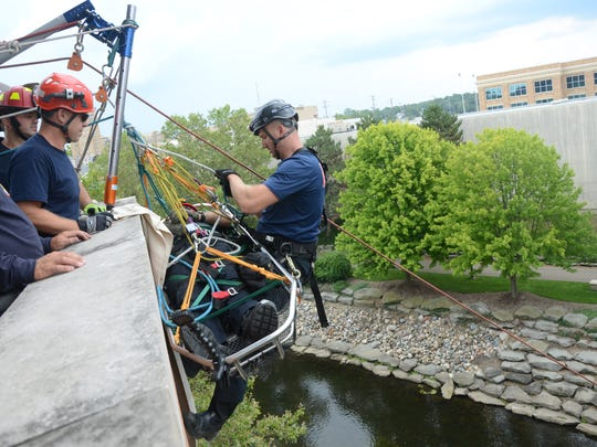 Battle Creek Firefighter Kurt Hoeksema, prepares to help guide the basket containing Captain Dan Wolfe to the ground Thursday, Aug. 3, 2017.