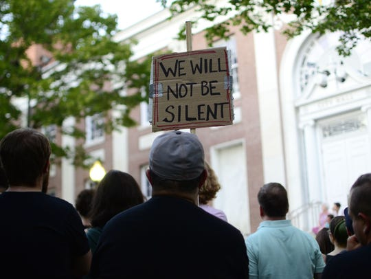 Sam Lurie of Monkton holds a sign during a speak-out