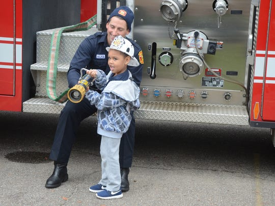 Firefighter Gary Metheny helps Rickey Ford, 4, handle