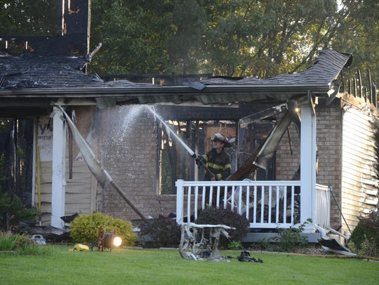 Firefighters continue to spray water on the remains