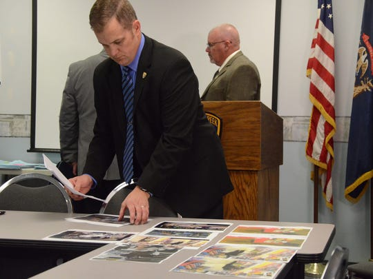 Detective Sgt. Todd Elliott of the Battle Creek Police Department displays photos of suspects in robberies.