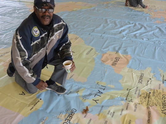 Ron Leigh recalled his travels while in the Navy after signing the 50 by 70 foot map.