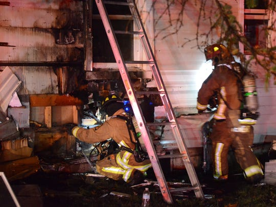 Firefighters peel siding from the outside of the house