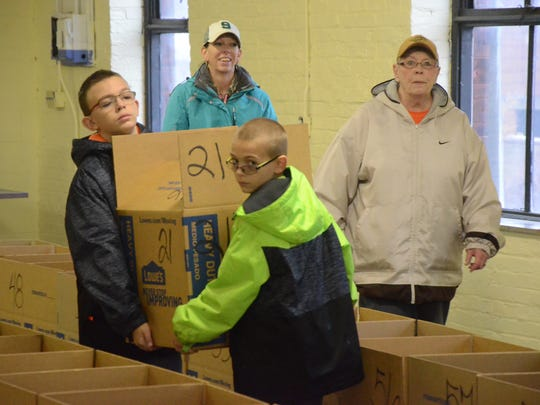 Brothers Marcus Hall, 12, left, and Ashton Hall, 10, carry a loaded box to a family. Their mother, April Hall, back left, and grandmother, Pam Arends, also helped pack the Thanksigiving meals.