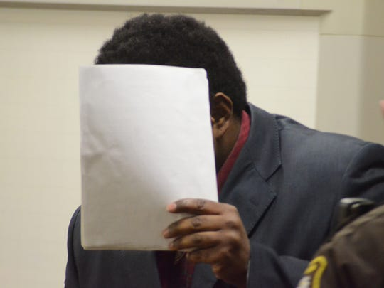 Devree Garner holds papers to avoid a photographer as he enters the courtroom Wednesday.