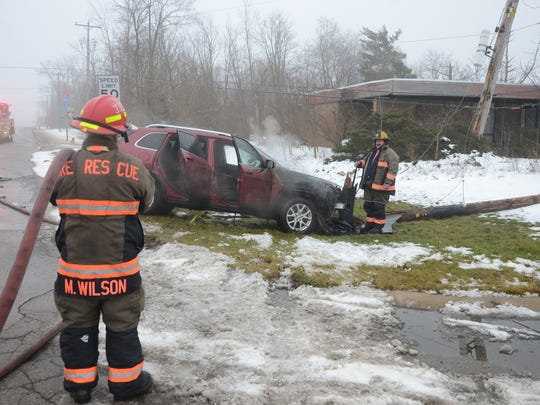 Two men suffered minor injuries after their car overturned, struck a power pole and caught fire.