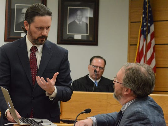Defense attorney Justin McCarthy, left questions Dr.
