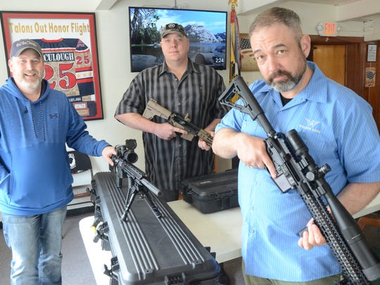 Alex Kahn, from left and Bill Thick Jr., of the VFW Post in Marshall and Chris Walden of Walden Arms in Battle Creek.