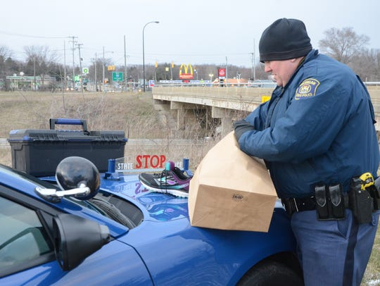 Michigan State Police Trooper Jason Mead collects some
