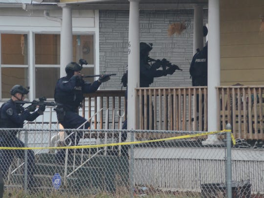 Battle Creek officers enter a home on Merritt Street Sunday after a shooting early Sunday, April 15, 2018.