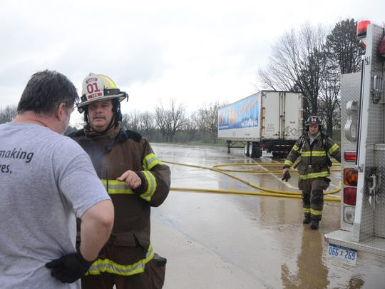 Tekonsha Township Fire Chief Daryl Cummins talks with trucker Jerry Schulz from Saginaw at the scene of a semi fire on Interstate-69 Thursday, as firefighter Ryan Rafferty approaches.