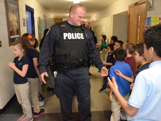 Tyler Sutherland greets students at Battle Creek Academy during a 2015 school visit while a member of the Gang Suppression Unit.