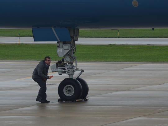 Ben Hammond, a manager at Duncan Aviation, places wheel chocks after the vice-presidential plane lands in Battle Creek.