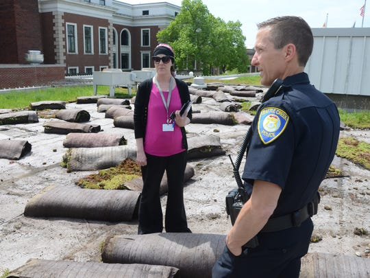 Tiffany Welsh, Battle Creek's environmental & storm service manager and Lt. Doug Bagwell look over the remains of the police department's green roof.