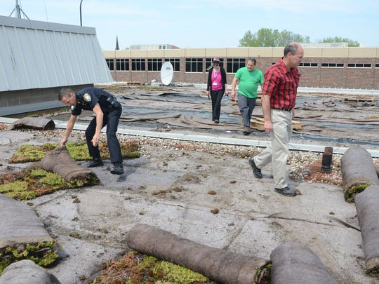 City employees, Lt. Doug Bagwell, from left, Tiffany Welsh, Darian Couturier and Kurt Tribbett, look over the remains of the green roof over the police station.