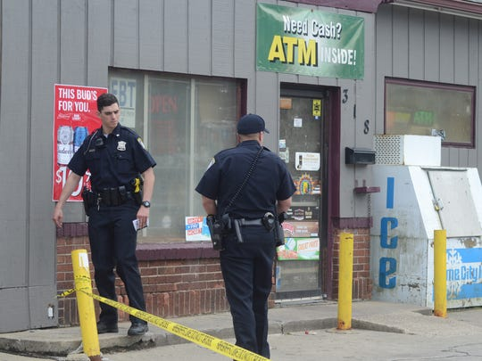 Police investigate outside the Dixie Mart on Wednesday.