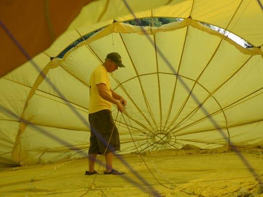 Steve Wilkinson of Palm Desert, Calif., checks lines inside the balloon before his Sunday flight.
