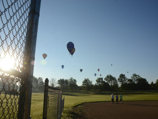 Hot air balloons approach the target on a baseball field on Tuesday.