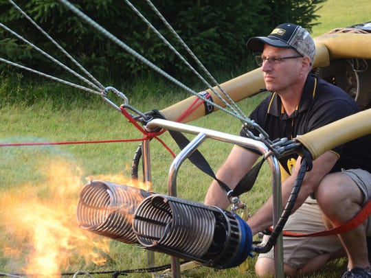 Pilot Rick Kerber of Wayland adds heat to his balloon during Wednesday morning inflation.
