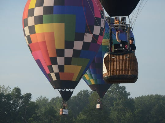 Chris Smart of Huntington, Ind. leads two other balloons into a target Wednesday morning.